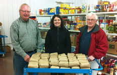 Bruce Street, President of the Crowsnest Pass Food Bank, accepts a donation of beef to the Crowsnest Pass Food Bank from  Dr. Kristy Penner (centre) and Dr. Allan Garbutt (right)
